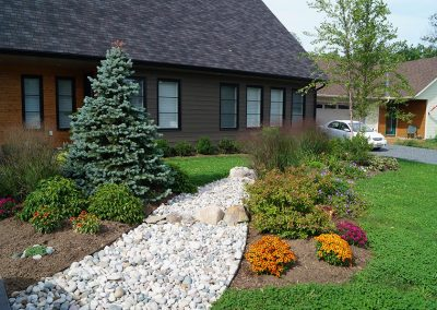 Dry riverbed through garden bed with grasses, perennials and shrubs
