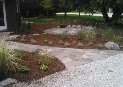 Flagstone patio and walkway through newly planted gardens with grasses